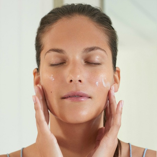 Woman massaging Pro-Collagen Marine Cream into face.