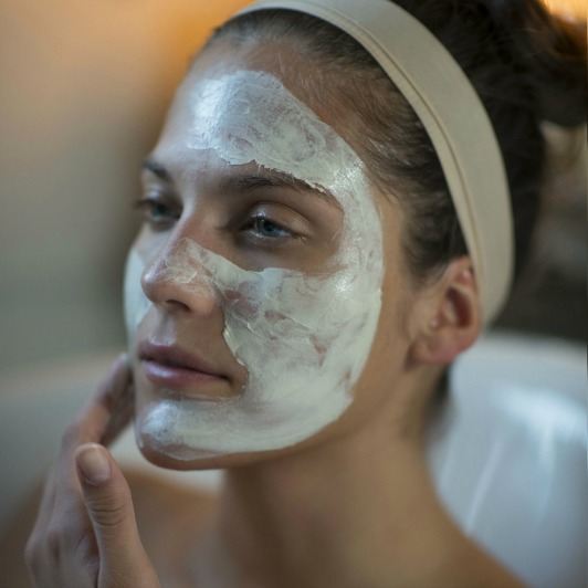 Woman applying Pro-Collagen Marine Mask to her face, avoiding the eye-area and the lips.