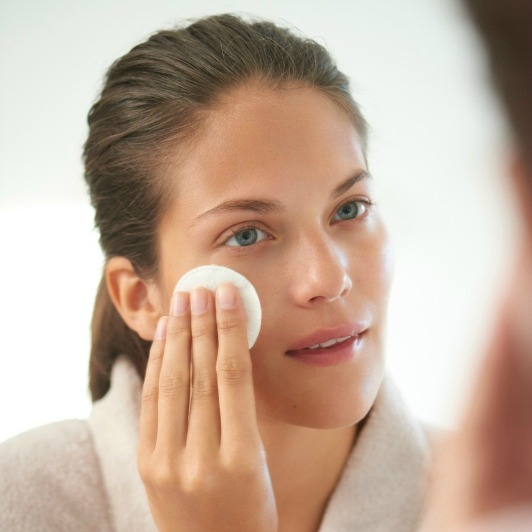 Woman in bathrobe wiping ELEMIS Rehydrating Ginseng Toner over face with a cotton pad.